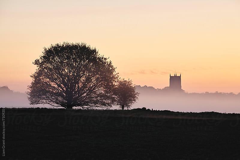 Rural church in fog at sunrise. Fakenham, Norfolk, UK. by Liam Grant for Stocksy United