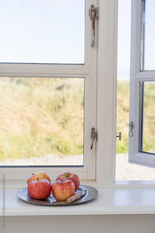 Apples in a wooden window with a view of the dunes by Elisabeth Coelfen for Stocksy United