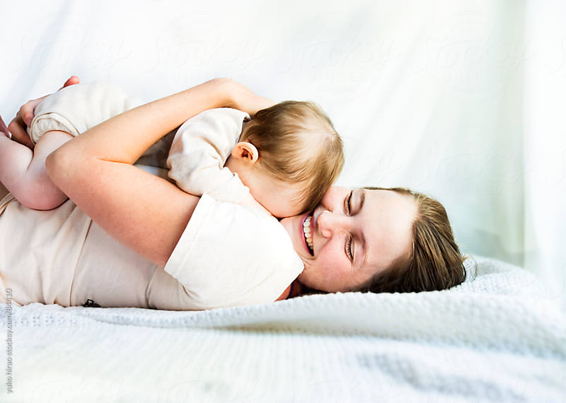 Mother, embracing a tired baby by yuko hirao for Stocksy United