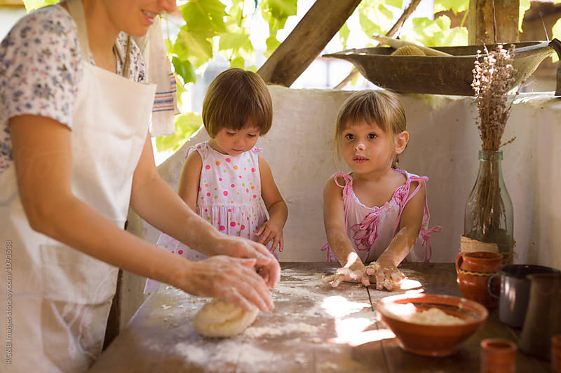 Girls making homamade bread with their mother by RG&B Images for Stocksy United