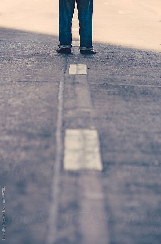 Man in jeans standing in middle of a street in black shoes by Soren Egeberg for Stocksy United