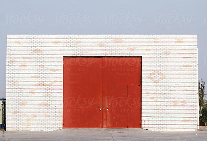 A warehouse with red gate in gas station by zheng long for Stocksy United