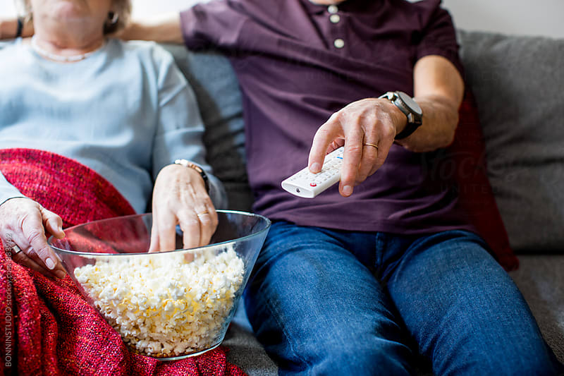 Closeup of an elderly couple watching tv eating popcorn at home. by BONNINSTUDIO for Stocksy United