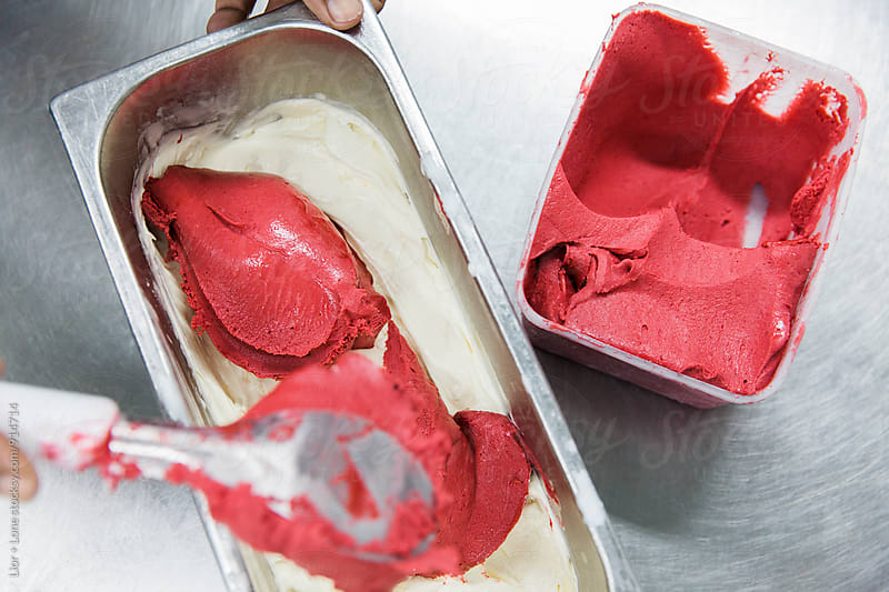 Person mixing strawberry and vanilla ice cream together by Lior + Lone for Stocksy United