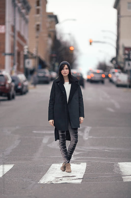 A young woman standing on a crosswalk by Ania Boniecka for Stocksy United