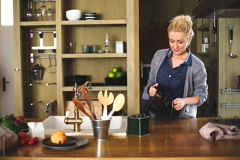 Woman Pours Herself Tea in the Kitchen by Lumina for Stocksy United