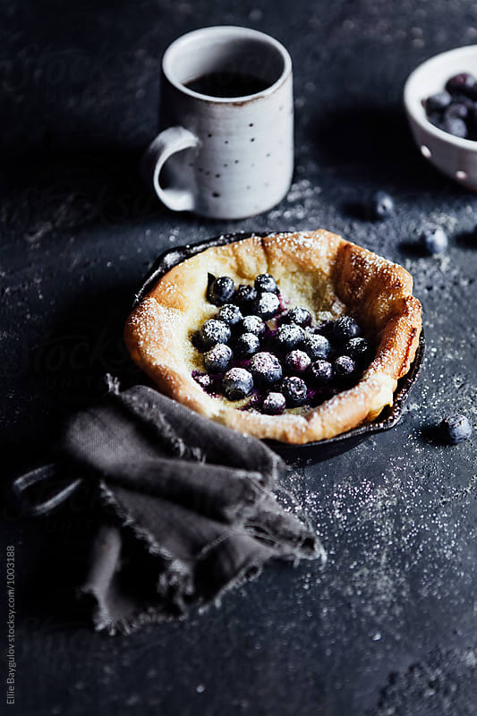 Mini blueberry Dutch baby pancake by Ellie Baygulov for Stocksy United