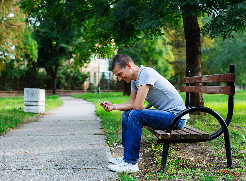 Young Man Sitting on the Park Bench and Checking Phone by Mosuno for Stocksy United