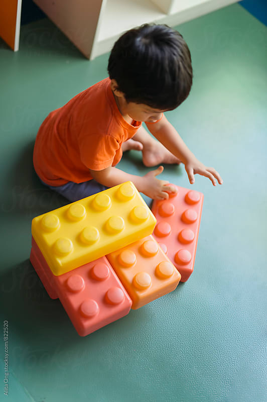 Child playing with large building blocks by Alita Ong for Stocksy United