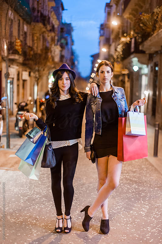 Portrait of two young women with many shopping bags standing on by BONNINSTUDIO for Stocksy United
