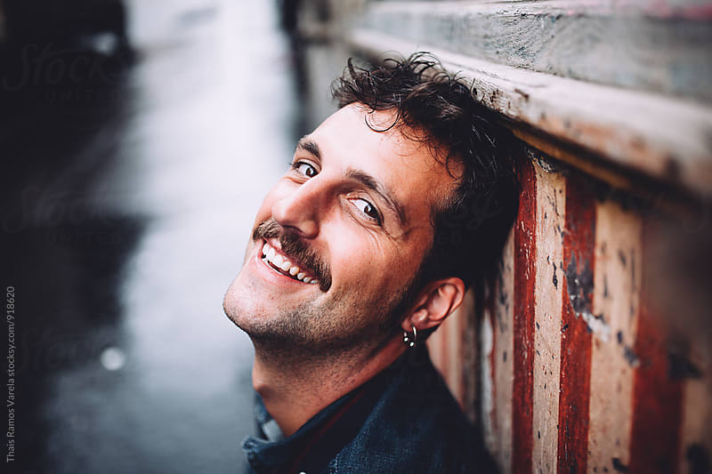 Man with moustache smiling by Thais Ramos Varela for Stocksy United