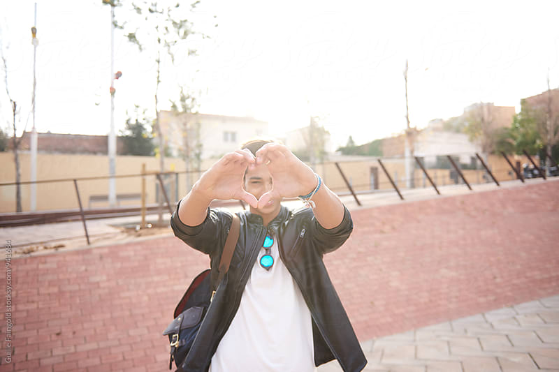 Smiling man making heart shape with hands by Guille Faingold for Stocksy United