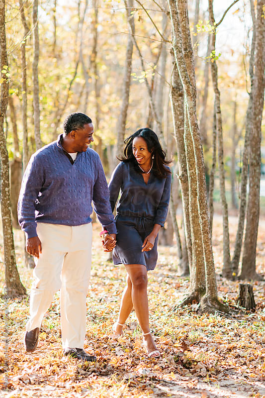 Portrait of a happily married African American couple walking through the park by Kristen Curette Hines for Stocksy United