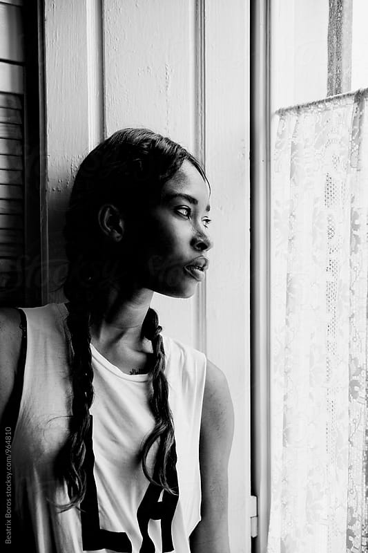 African American woman with braids looking out of the window by Beatrix Boros for Stocksy United