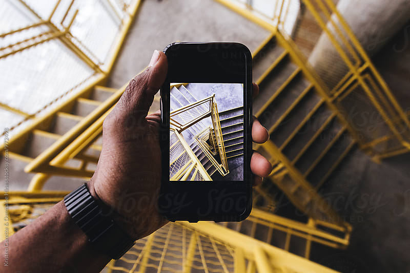 A man with a smart phone taking a photograph of a stairwell by Kristen Curette Hines for Stocksy United