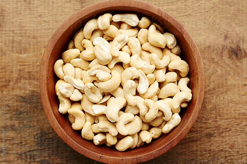 Cashew nuts in a wooden bowl by Harald Walker for Stocksy United