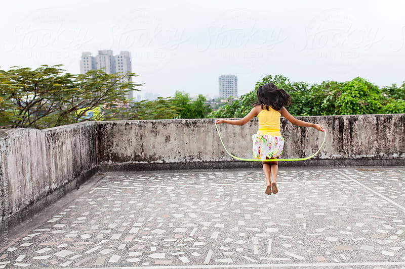 A teenager doing exercise with a jumping rope in a roof top of urban area by PARTHA PAL for Stocksy United