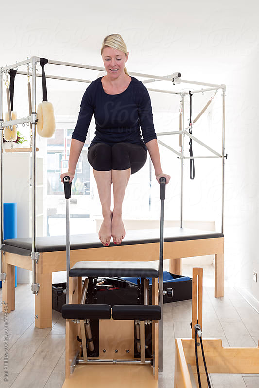 Exercise being performed above the Pilates Wunda Chair. Bright studio. by Paul Phillips for Stocksy United