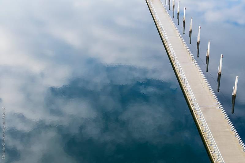 Walkway over lake with sky reflection by Melanie Kintz for Stocksy United