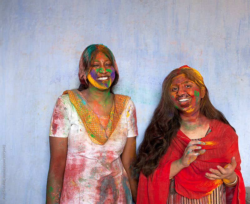 Indian woman celebrating Holi with colored spray power  by PARTHA PAL for Stocksy United