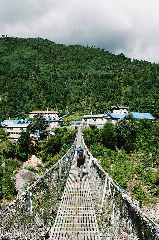 Female trekker crossing a swing bridge, Everest Region, Sagarmatha National Park, Nepal. by Thomas Pickard for Stocksy United