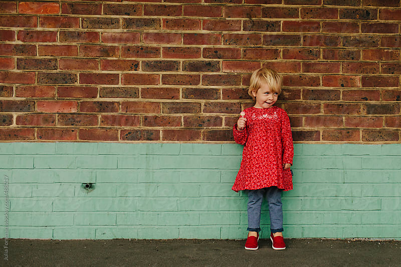 Toddler girl against brick wall. by Julia Forsman for Stocksy United