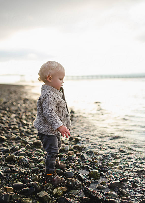 Profile of a Toddler Boy on a rocky shore at sunset by Amanda Voelker for Stocksy United