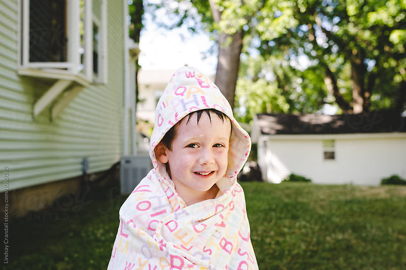Smiling child wrapped in towel after swimming by Lindsay Crandall for Stocksy United