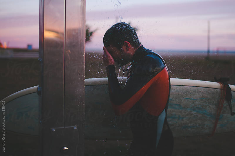 Surfer taking shower after session by Leandro Crespi for Stocksy United