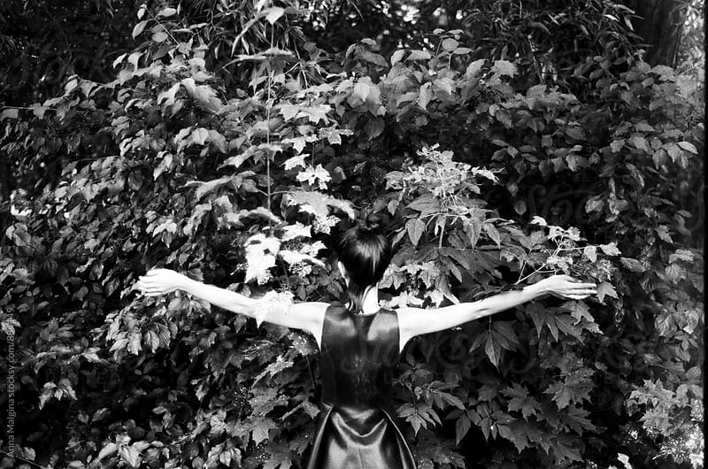 A black and white back portrait of a young woman hugging a bush tree by Anna Malgina for Stocksy United