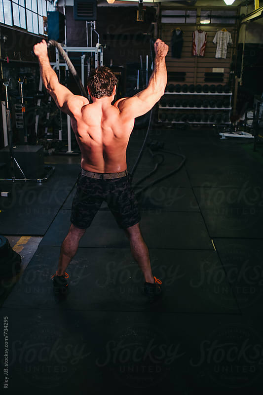 A shirtless, muscular man exercises using battling ropes by Riley Joseph for Stocksy United