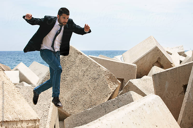Businessman jumping on breakwater. by BONNINSTUDIO for Stocksy United