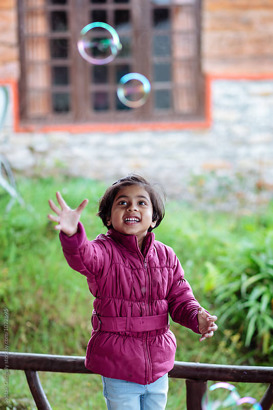 Little girl trying to catch soap bubbles by Saptak Ganguly for Stocksy United