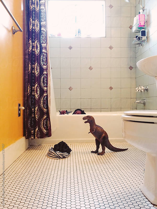 Young girl in bath with dinosaur  by Kristin Rogers Photography for Stocksy United
