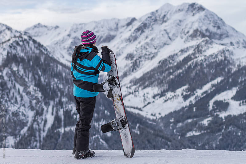 Female Snowboarder in alpine scenery by Leander Nardin for Stocksy United