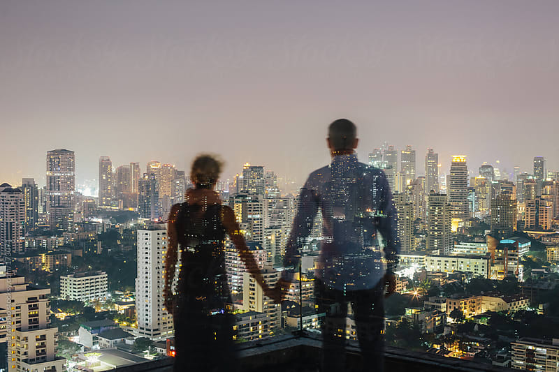 Couple looking the cityscape from the roof by michela ravasio for Stocksy United