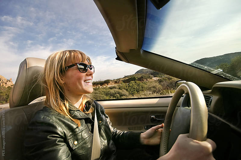 Excited young woman driving a convertible by Per Swantesson for Stocksy United