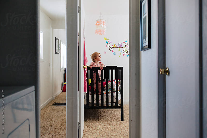 Toddler standing in crib after a nap by Jessica Byrum for Stocksy United