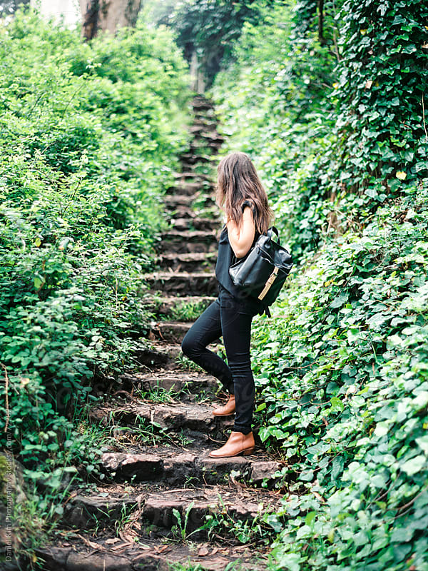 Woman walking up forest steps by Daniel Kim Photography for Stocksy United
