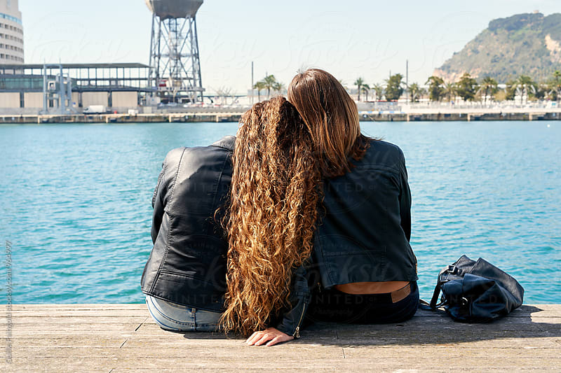 Back view of two friends on pier by Guille Faingold for Stocksy United