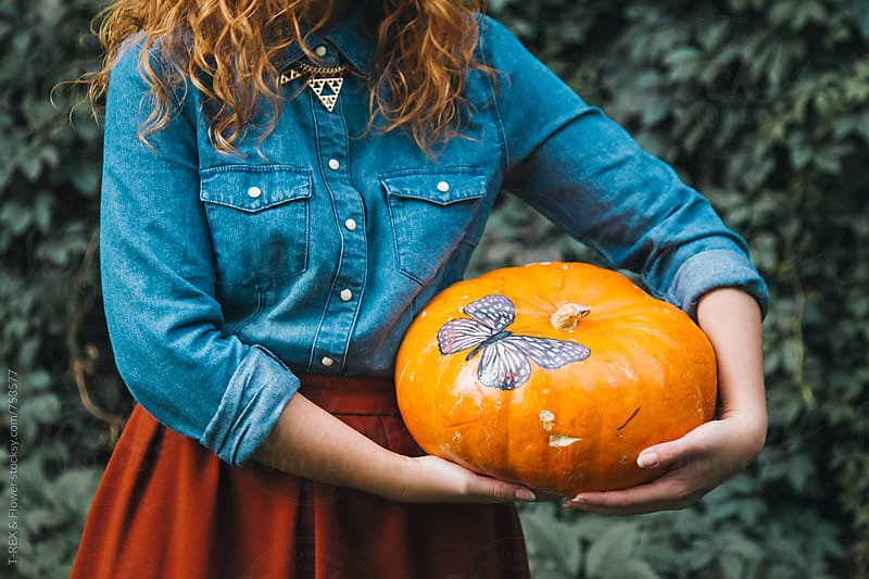 Woman holding orange pumpkin in hands by T-REX & Flower for Stocksy United