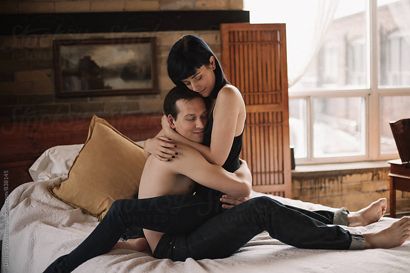 Young topless lovers hugging on bed in industrial loft bedroom by Daring Wanderer for Stocksy United