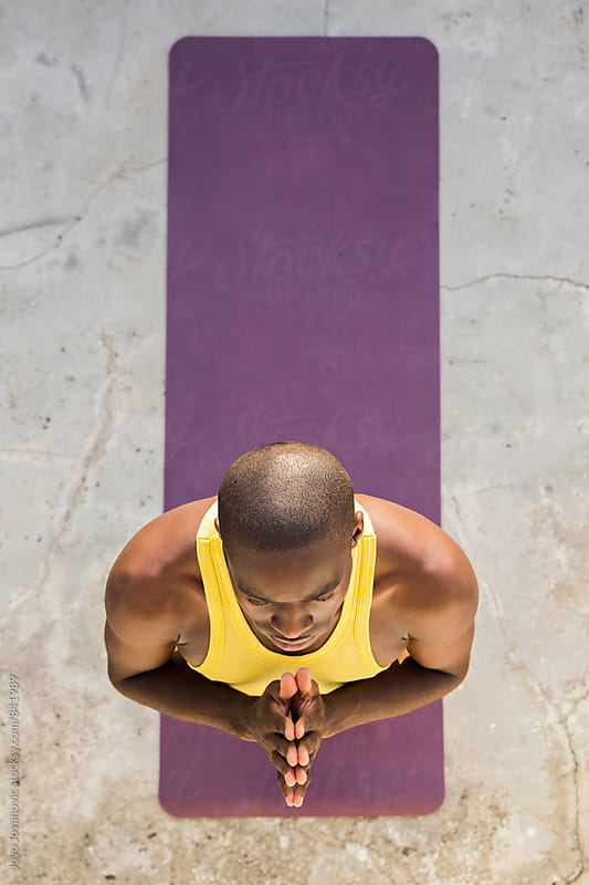 Handsome young man standing up with his hands in a namaste position by Jovo Jovanovic for Stocksy United