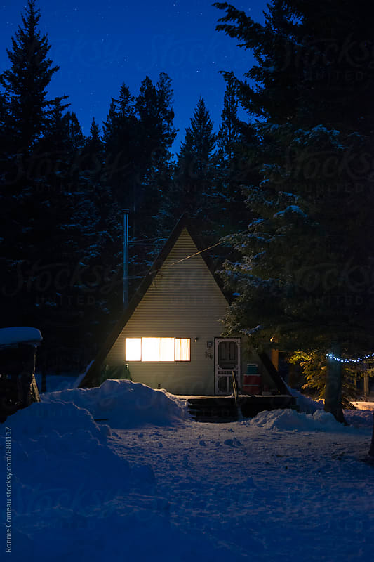 A-Frame Cabin In The Woods In Winter And At Night by Ronnie Comeau for Stocksy United