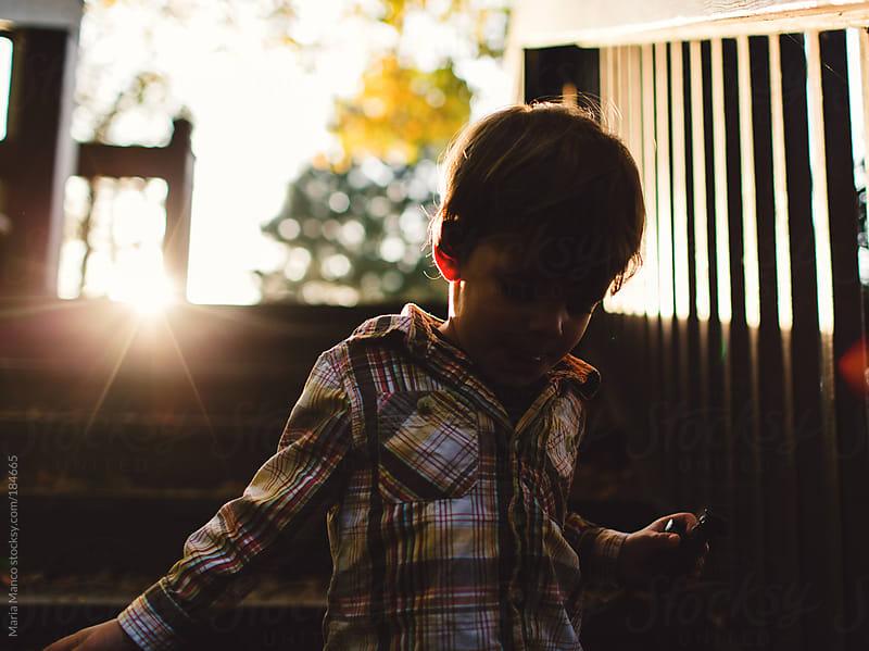 boy walks down steps in sunlight by Maria Manco for Stocksy United