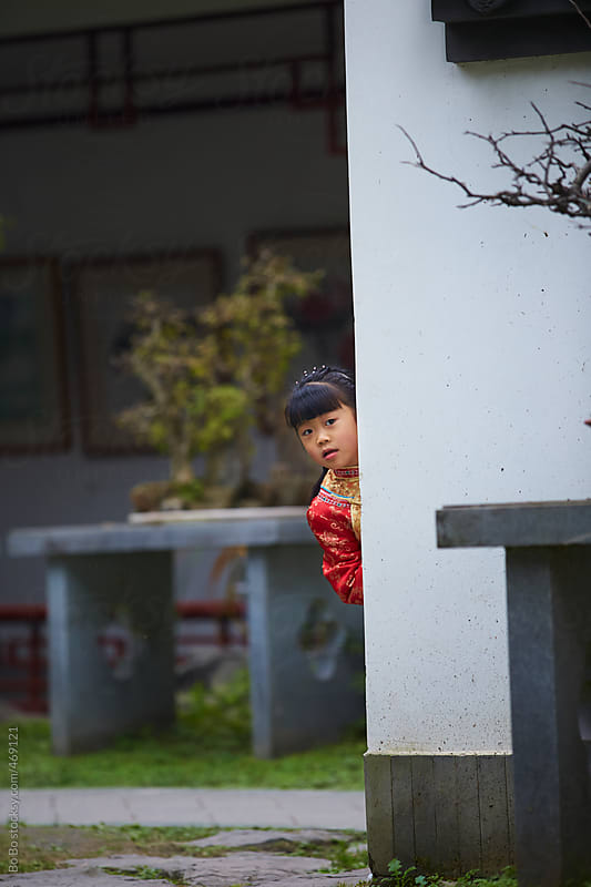 little Chinese girl hiding behind the wall in the park by Bo Bo for Stocksy United