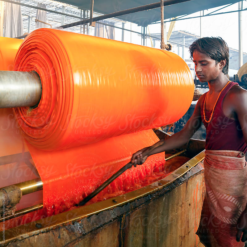 Portrait of a factory worker, Newly dyed fabric being washed and rolled, Sari garment factory, Jaipur, Rajasthan, India by Gavin Hellier for Stocksy United