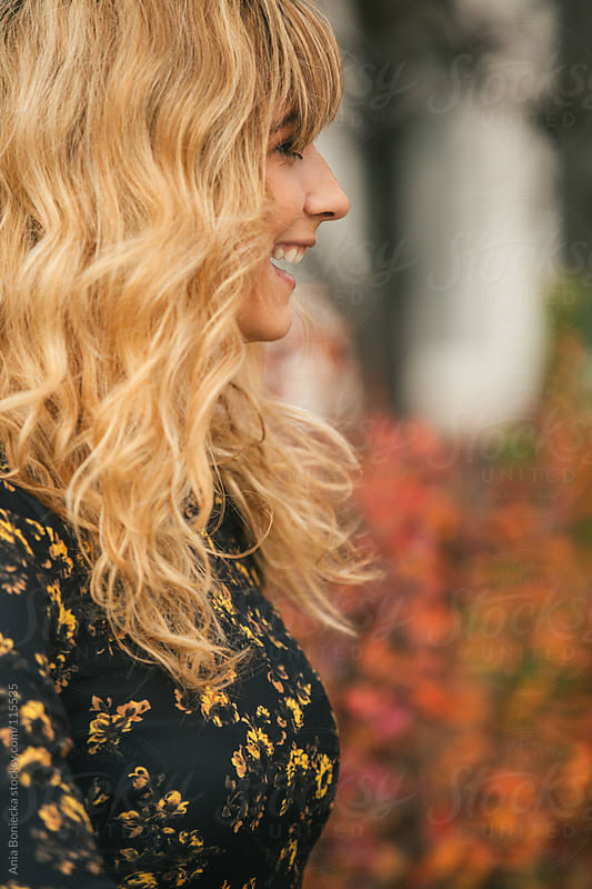 A profile portrait of a laughing blonde woman in the fall by Ania Boniecka for Stocksy United