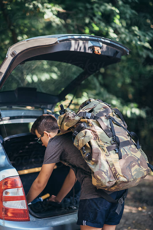 Young teen boy with a backpack searching in the car's trunk by Adrian Cotiga for Stocksy United