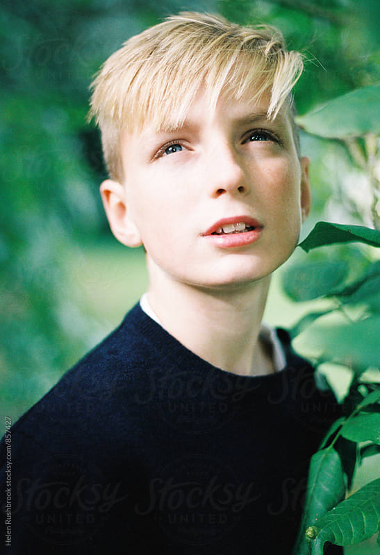 Portrait of a teenage boy outdoors. Looking away from camera. by Helen Rushbrook for Stocksy United
